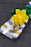 Cutlery serving with one daffodil flower Royalty Free Stock Photos