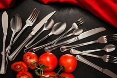 Cutlery set banquet guests black background. Silver cutlery set on black background with red color accents. Table setting for banquet concept Stock Photography