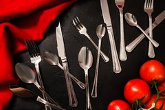 Cutlery set banquet guests black background. Silver cutlery set on black background with red color accents. Table setting for banquet concept Stock Image