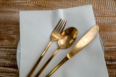 Cutlery set, brass Fork, Knife and Spoon on a wooden table Stock Photography