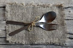 Cutlery set:fork and spoon on burlap cloth on rustic wooden table.Cutlery on old wooden background.Can be used as background menu. For restaurant.Selective Royalty Free Stock Images