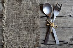 Cutlery set:fork and spoon on burlap cloth on rustic wooden table.Cutlery on old wooden background.Can be used as background menu. For restaurant.Selective royalty free stock photo