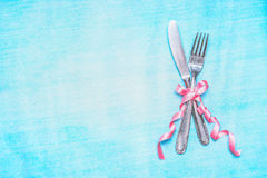 Cutlery set with pink ribbon on light blue background, top view, place for text. Stock Images