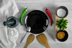 Cutlery set with spices and mortar on wood table background. Cutlery set with spices, chillies and mortar on wood table background. Kitchen utensils Stock Photos