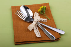 Cutlery. Spoon with fork wrapped with ribbon and lay on a napkin with a flower on wooden green table Stock Photo
