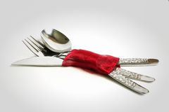 Cutlery. Spoon, knife, fork tied with a red ribbon Royalty Free Stock Photography