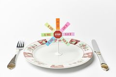 Cutlery and stop sign with banned additives stock image