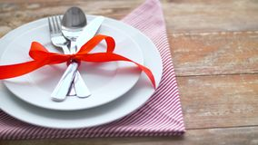 Cutlery tied with red ribbon on plate stock footage