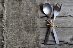Cutlery ustawiający: rozwidlenie i łyżka na burlap płótnie na nieociosanym drewnianym stole Cutlery na starym drewnianym tle Może zdjęcie royalty free