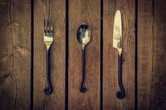 Cutlery - Vintage Fork, Spoon and Knife on Wood Background Stock Photo