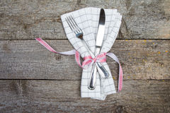 Cutlery on white checkered napkin tied with red ribbon Stock Photo