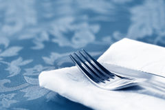 Cutlery on White Linen Over Brocade. Knife and fork on white linen napkin, over brocade tablecloth Stock Photo