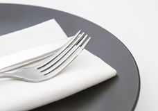 Cutlery on white napkin and plate Stock Image