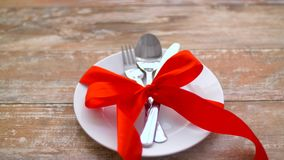 Cutlery wiążący z czerwonym faborkiem na talerzu zbiory