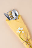 Cutlery wrapped in a yellow napkin on a light peach background. Royalty Free Stock Photography