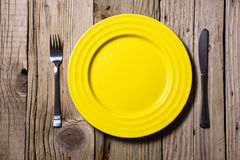 Cutlery and yellow plate on  wooden Royalty Free Stock Image