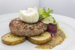 Cutlet σε ένα μαξιλάρι των πατατών με το μαρούλι, κυνήγησε λαθραία αυγό και πικάντικος ζωμός στοκ φωτογραφίες με δικαίωμα ελεύθερης χρήσης