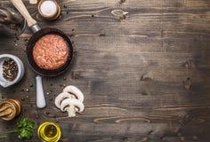Cutlet του επίγειου βόειου κρέατος μικρά τηγανίζοντας παν, τεμαχισμένα μανιτάρια, πιπέρι, χορτάρια και αλατισμένα σύνορα, ξύλινη  Στοκ Εικόνα