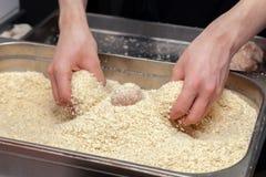 Χέρια αρχιμαγείρων που δημιουργούν, διαμόρφωση, πασπαλίζοντας με ψίχουλα cutlet κοτόπουλου με το μαχαίρι στην επαγγελματική κουζί στοκ φωτογραφία με δικαίωμα ελεύθερης χρήσης