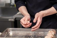 Χέρια αρχιμαγείρων που δημιουργούν, διαμόρφωση, πασπαλίζοντας με ψίχουλα cutlet κοτόπουλου με το μαχαίρι στην επαγγελματική κουζί στοκ εικόνες