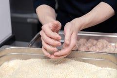 Χέρια αρχιμαγείρων που δημιουργούν, διαμόρφωση, πασπαλίζοντας με ψίχουλα cutlet κοτόπουλου με το μαχαίρι στην επαγγελματική κουζί στοκ εικόνα με δικαίωμα ελεύθερης χρήσης