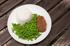 Cutlet dinner with rice and green peas Royalty Free Stock Image