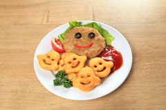 Cutlet with garnish on a plate on the table. In the children`s  restaurant Royalty Free Stock Images