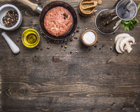 Cutlet of ground beef in a small frying pan, sliced mushrooms, pepper, herbs and salt border ,place text wooden rustic back Royalty Free Stock Photography