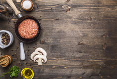 Cutlet of ground beef in a small frying pan, sliced mushrooms, pepper, herbs and salt border ,place text wooden rustic back Stock Image