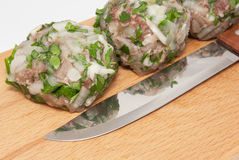Cutlet and knife on wooden board Stock Image