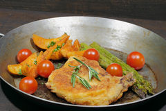 Cutlet with potato wedges, tomatoes, green asparagus, garnished Royalty Free Stock Photography