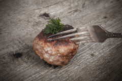 Cutlet and slice on a fork on old wooden table. Tinted Stock Photo