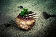 Cutlet and slice on a fork on old wooden table.Tinted Royalty Free Stock Images