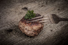 Cutlet and slice on a fork on old wooden table. Tinted Royalty Free Stock Photography