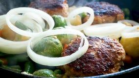 Cutlets και τα λαχανικά είναι τηγανισμένα στο ηλιέλαιο στο τηγάνισμα του τηγανιού E Φασόλι, καρότα, κουνουπίδι απόθεμα βίντεο