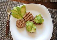 Cutlets φαγόπυρου σχάρα και φέτες του αβοκάντο σε ένα άσπρο πιάτο Ένα δίκρανο με μια ξύλινη λαβή πρόγευμα υγιές Στοκ Εικόνα