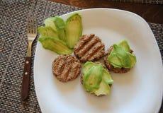 Cutlets φαγόπυρου σχάρα και φέτες του αβοκάντο σε ένα άσπρο πιάτο Ένα δίκρανο με μια ξύλινη λαβή πρόγευμα υγιές Στοκ Φωτογραφία
