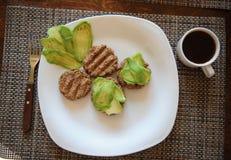 Cutlets φαγόπυρου σχάρα και φέτες του αβοκάντο στο άσπρο πιάτο Δίκρανο με την ξύλινη λαβή Φλιτζάνι του καφέ πρόγευμα υγιές Στοκ φωτογραφία με δικαίωμα ελεύθερης χρήσης