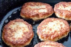 Cutlets ψήνονται σε ένα μαύρο τηγανίζοντας τηγάνι στοκ φωτογραφία