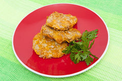 Cutlets breaded. With corn flakes on the red plate Royalty Free Stock Photos