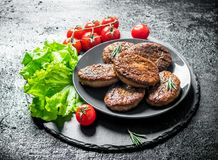 Cutlets with cherry tomatoes and salad leaves. On black rustic background royalty free stock image