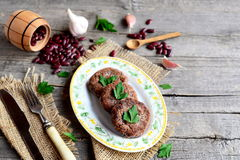 Cutlets cooked from mashed red beans. Vegetarian cutlets, scattered raw red beans, garlic, fresh parsley, fork, knife Stock Photos
