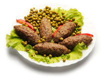 Cutlets, decorated peas and paprika. On white background Royalty Free Stock Photo