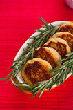 Cutlets with fresh rosemary. On plate located on red bamboo napkin Stock Photos