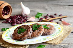 Cutlets made from boiled and mashed red beans on a plate. Scattered uncooked red beans, garlic, fresh parsley, small wooden spoon Stock Photo
