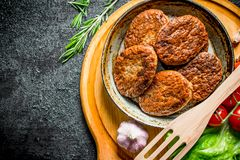 Cutlets at the old pan with a spatula, cherry tomatoes and salad leaves. On black rustic background royalty free stock images
