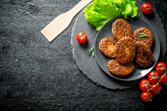 Cutlets on a plate with salad leaves and tomatoes. On black rustic background royalty free stock images