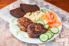 Cutlets with tomatoes and cucumbers Royalty Free Stock Photo