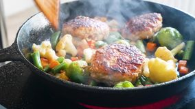 Cutlets and vegetables are fried in sunflower oil in frying pan. Close-up. Bean, carrots, cauliflower. Cutlets and vegetables are fried in sunflower oil in stock video footage