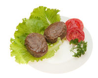Cutlets with vegetables on a plate Stock Images
